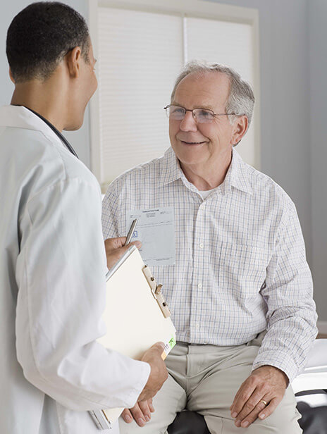 A doctor looking at the appointment card of an aged patient